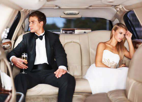pareja de recién casados en limusina mirando cada uno a un lado