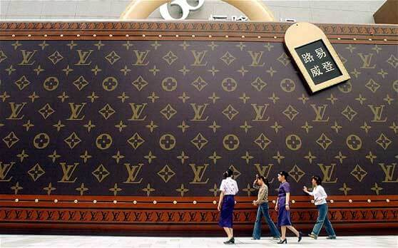 Chinos frente a una valla de Louis Vuitton en China