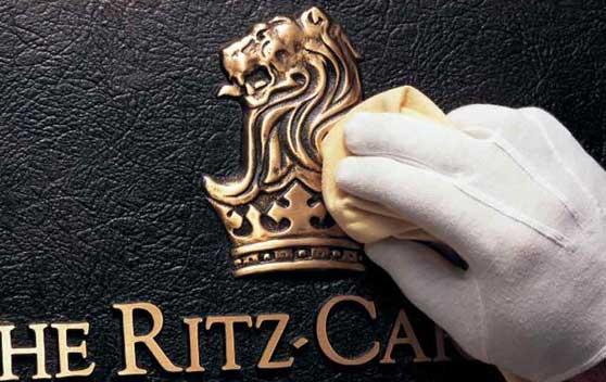 guante blanco sacando brillo al Logo Ritz Carlton para satisfacer al cliente más exigente