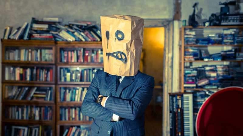 hombre en traje con bolsa de cartón en la cabeza biblioteca de fondo