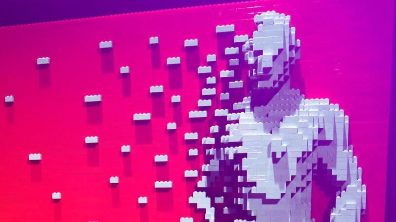 Figura humana tridimensional hecha con piezas de lego blancas con fondo rosado